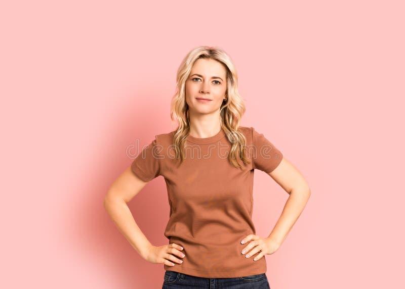 Ritratto sorridente attraente adulto della donna bionda bello, ragazza caucasica su fondo rosa fotografie stock libere da diritti