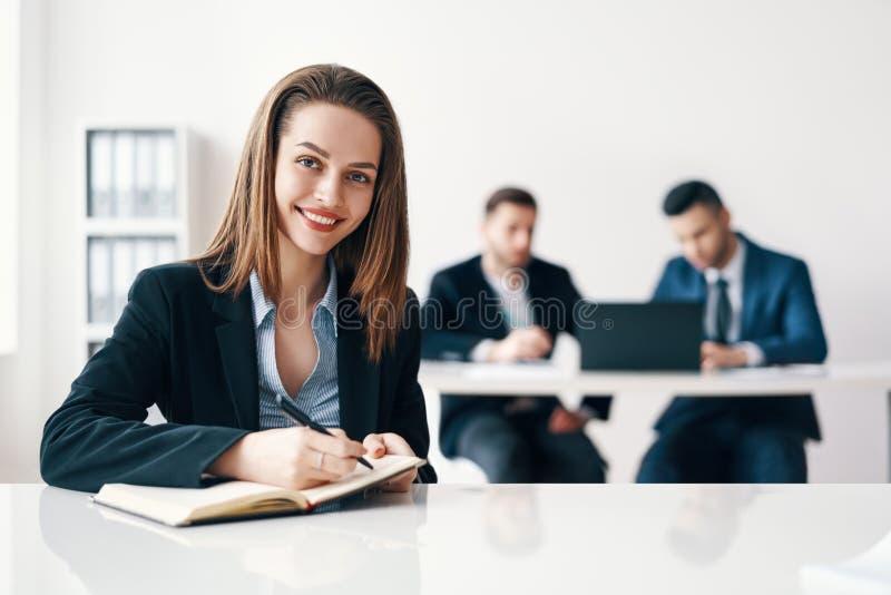 Ritratto sorridente felice della donna di affari che si siede nell'ufficio e che fa le note con il suo gruppo di affari sul fondo fotografia stock