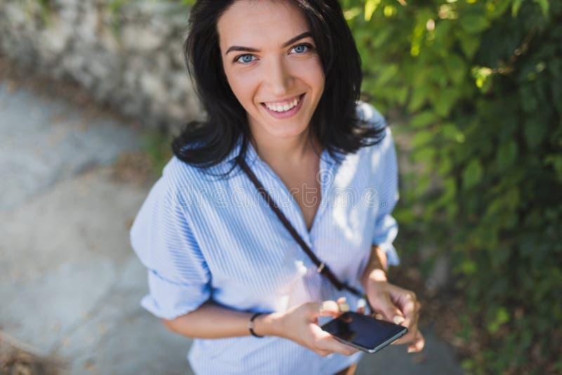 Ritratto sparato sopraelevato della donna attraente felice con il telefono cellulare che guarda alla macchina fotografica ed all' fotografia stock