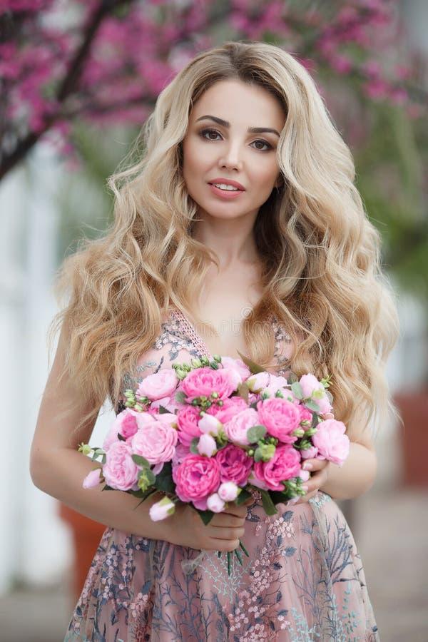 Ritratto splendido di una ragazza bionda in un vestito rosa sexy da sera con un mazzo di belle rose immagini stock