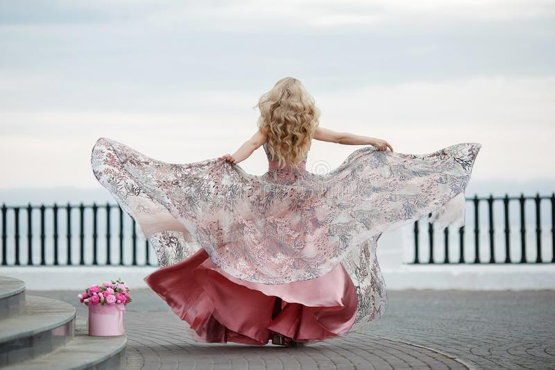 Ritratto splendido di una ragazza bionda in un vestito rosa sexy da sera con un mazzo di belle rose fotografie stock libere da diritti