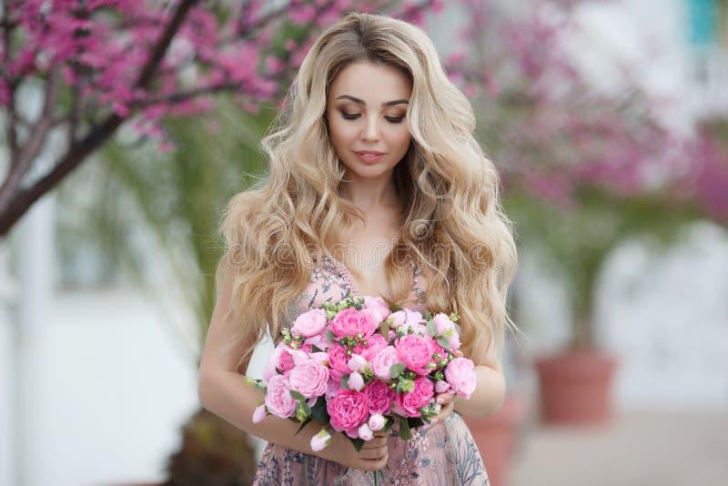 Ritratto splendido di una ragazza bionda in un vestito rosa sexy da sera con un mazzo di belle rose fotografia stock libera da diritti
