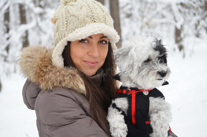 Ritratto sulla bella donna che abbraccia il suo cane nella foresta di inverno immagine stock