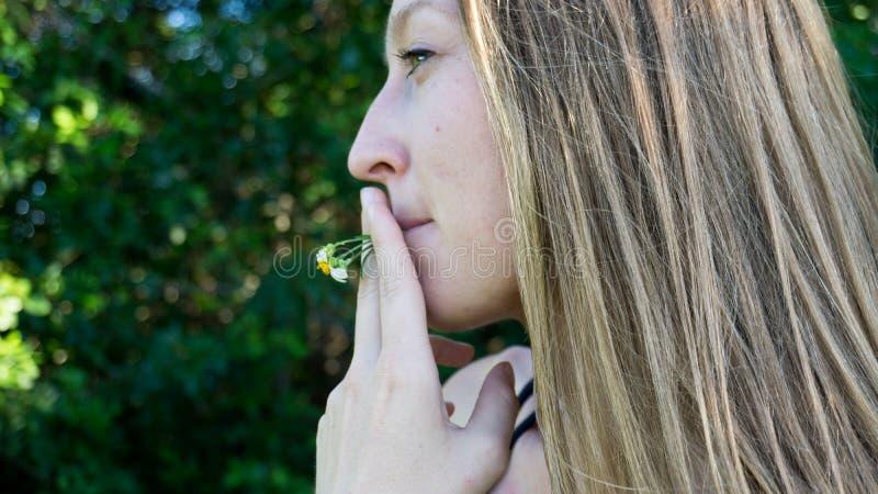 Ritratto sveglio dell'erbaccia di fumo del fiore della margherita del giovane fronte biondo della donna che sorride con i chiari  immagini stock libere da diritti