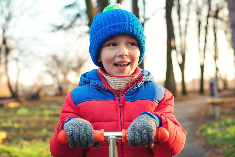 Ritratto sveglio di aria aperta del ragazzino Il bambino felice in vestiti caldi sta guidando il motorino al parco di autunno Inf immagini stock libere da diritti
