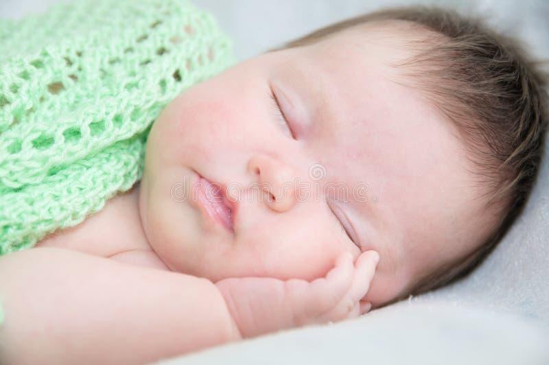 Ritratto sveglio infantile di sonno del bambino che si trova sulle armi fotografia stock