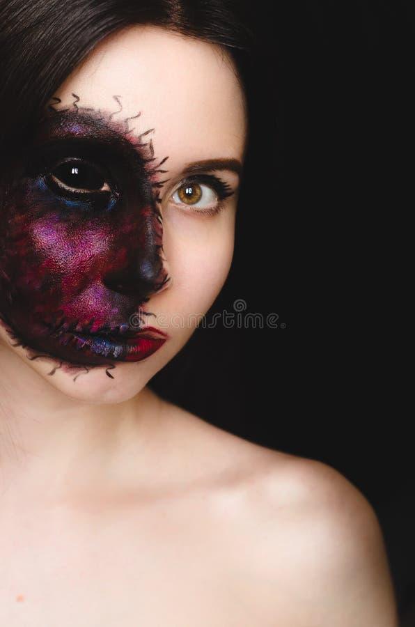 Ritratto terrificante di una donna con un segno maledetto sul suo fronte su fondo scuro fotografie stock libere da diritti