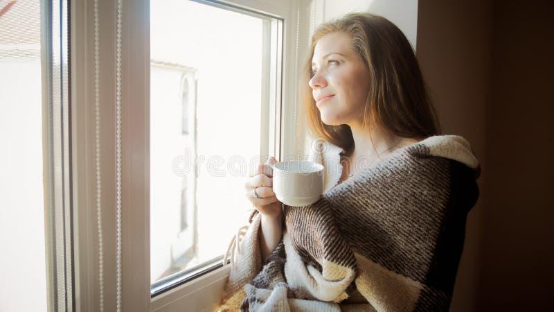 Ritratto tonificato della giovane donna sorridente in plaid che guarda dalla finestra fotografie stock