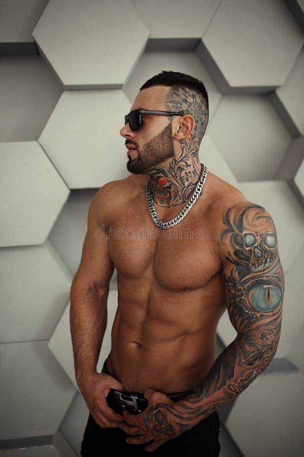 Ritratto topless del primo piano sexy del modello maschio bello elegante con il tatuaggio di modo e una condizione e una posa ner fotografia stock libera da diritti