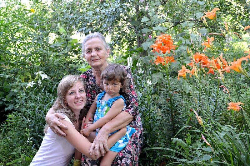 Ritratto in un giardino, tre generazioni della famiglia fotografie stock