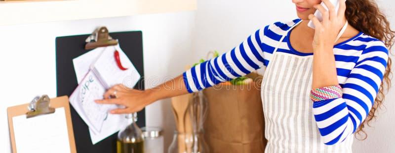 Ritratto un invio di messaggi di testo sorridente della donna delle verdure in cucina a casa immagini stock libere da diritti