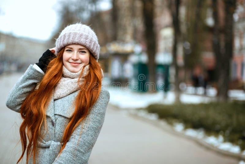 Ritratto urbano della donna felice della testarossa con la guerra d'uso dei capelli lunghi immagini stock