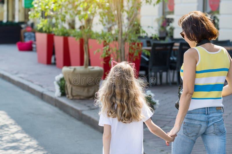 Ritratto urbano della figlia del bambino e della madre Vista posteriore immagini stock libere da diritti
