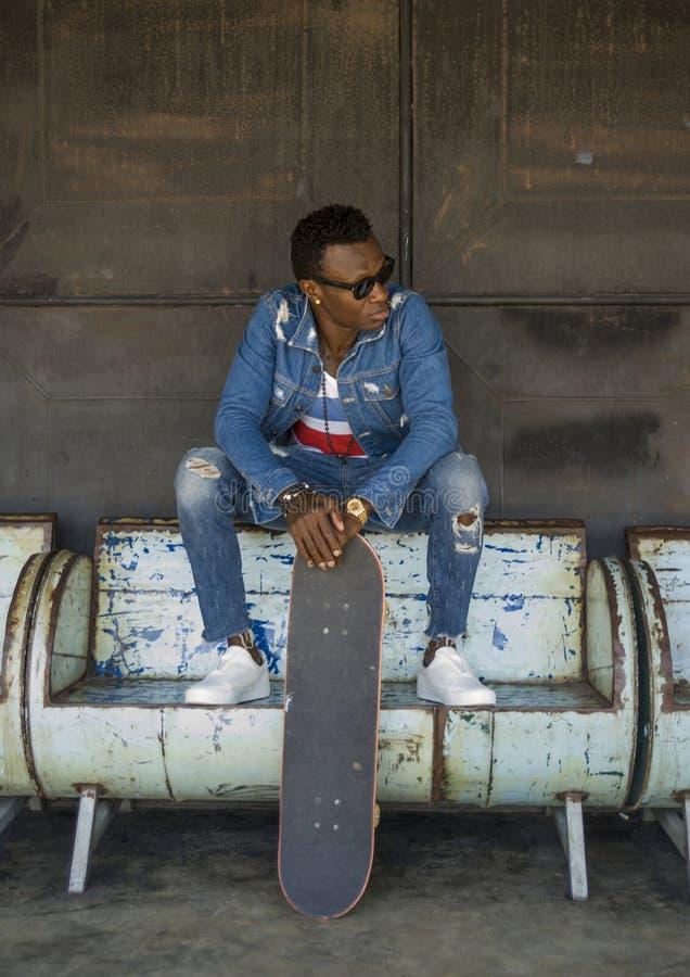 Ritratto urbano di stile di vita di giovane uomo afroamericano nero bello ed attraente del skateboarder che si siede sul banco di immagine stock