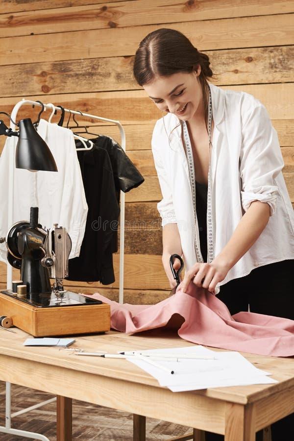 Ritratto verticale del sarto femminile entusiasta felice che sorride mentre godendo del suo lavoro in officina, tagliente tessuto fotografie stock