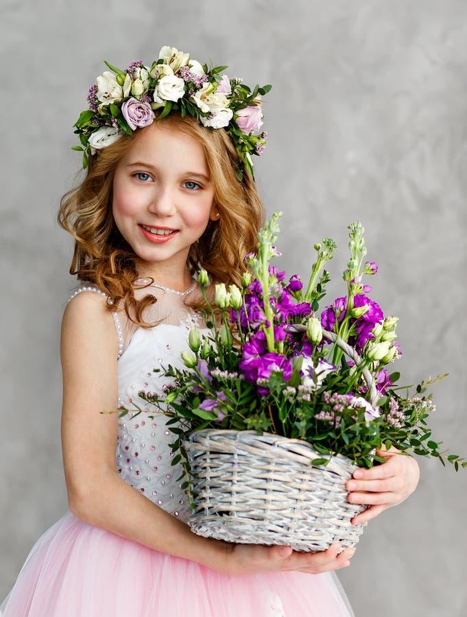 Ritratto verticale di bella bambina sveglia in una corona dei fiori freschi sulla sua testa ed in un canestro di bella molla fotografia stock