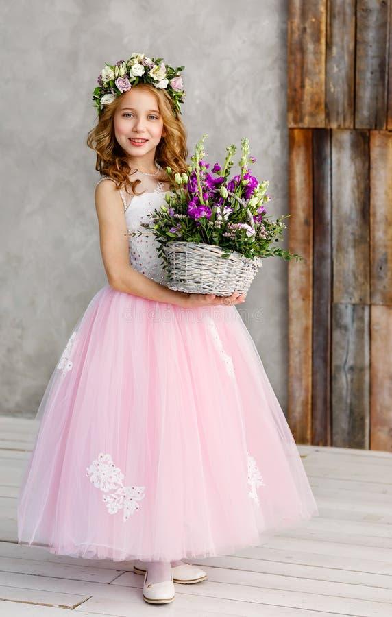 Ritratto verticale di bella bambina sveglia in una corona dei fiori freschi sulla sua testa ed in un canestro di bella molla fotografie stock libere da diritti