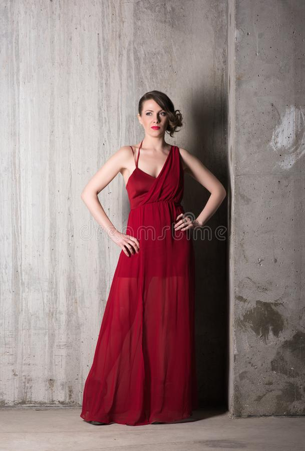 Ritratto verticale di bella giovane donna in vestito rosso lungo nella piena crescita immagine stock libera da diritti