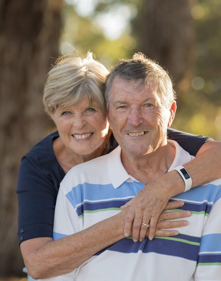 Ritratto verticale di belle e coppie mature felici senior americane intorno 70 anni che mostrano il toge sorridente di affetto e  immagini stock