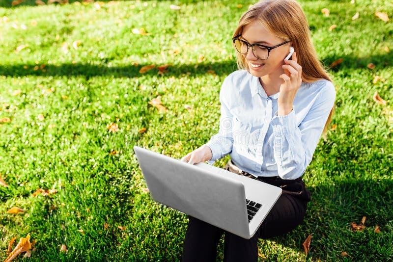 Ritratto vetri d'uso di giovani di una donna di affari, sedendosi sull'erba verde nel parco, lavorando facendo uso di un computer immagini stock