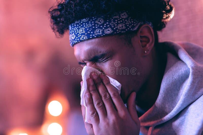 Ritratto vicino del giovane di origine africana con il tovagliolo vicino al suo fronte sui precedenti vaghi fotografie stock