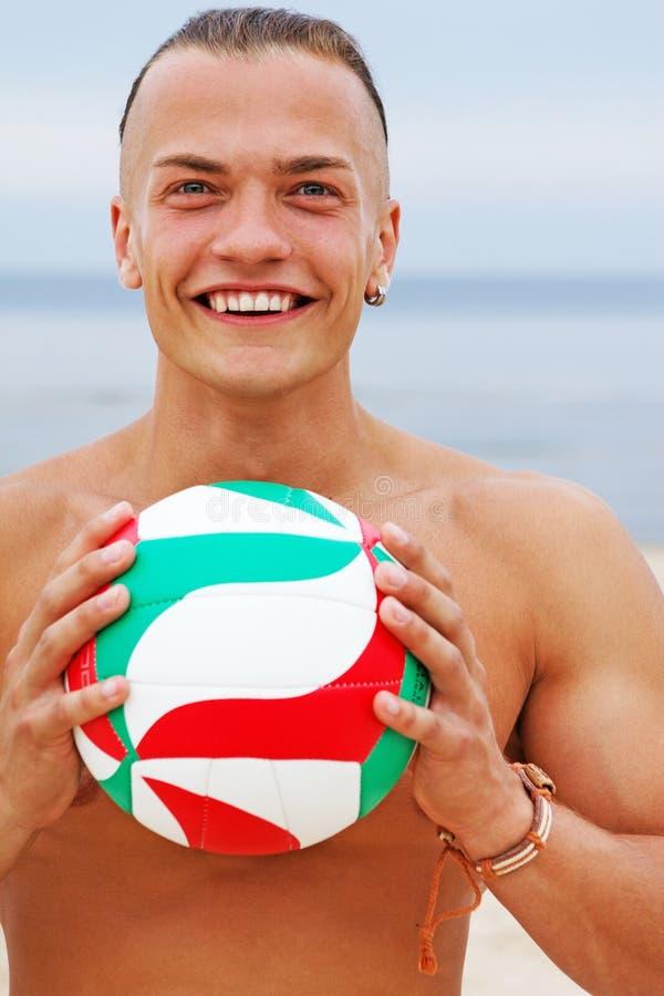 Ritratto vicino dell'uomo sorridente che posa sulla spiaggia con la palla fotografie stock libere da diritti