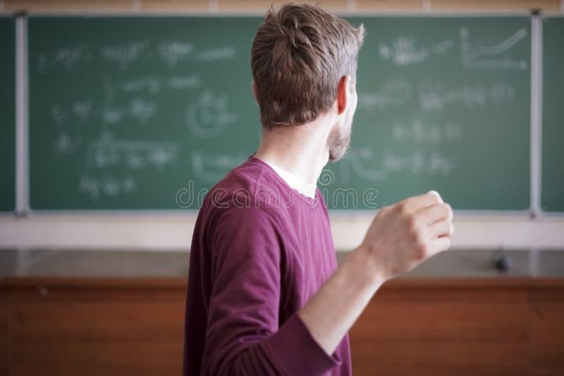 Ritratto vicino di giovane insegnante barbuto di professore in casuale con la lavagna con le formule dietro fotografia stock libera da diritti
