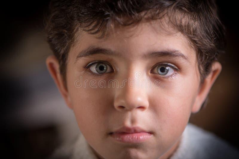 Ritratto vicino di osservazione di giovane ragazzo sveglio con gli occhi espressivi immagine stock libera da diritti