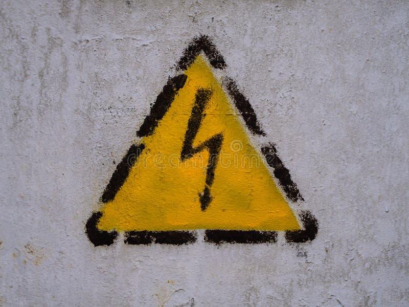 Ritssluitingsteken in de gele driehoek op de gemeenschappelijke muur royalty-vrije stock afbeelding