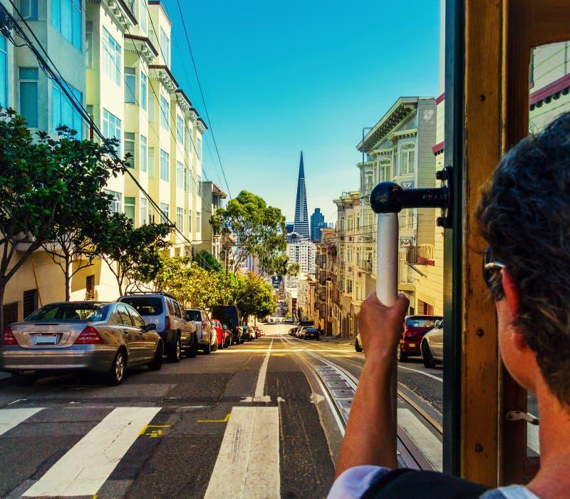 Ritt med kabelbilen i San Francisco Bilden visar en person som rider det berömda MUNIdrevet på Powell-murare linje royaltyfri fotografi