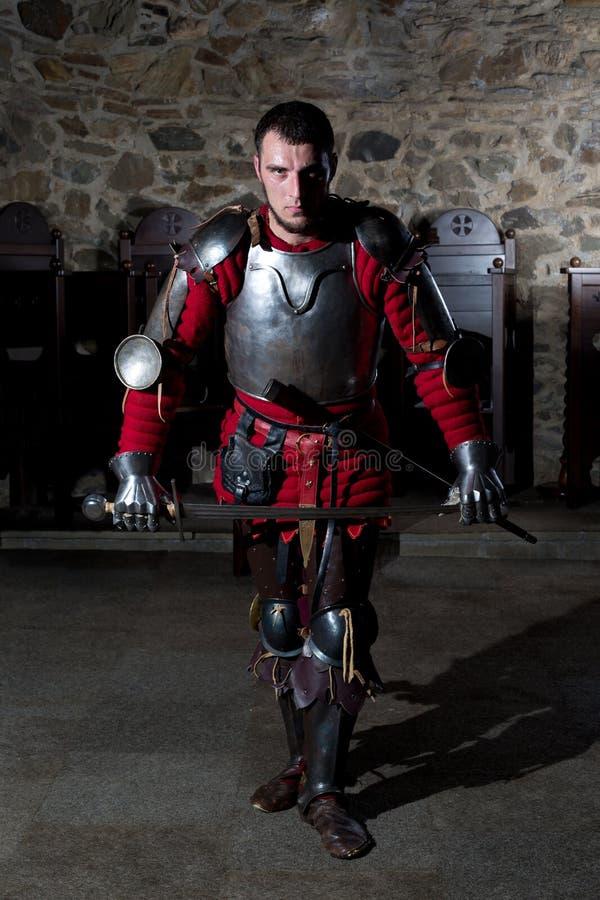 Ritter in Armor With Sword Standing in der alten Kirche und im Betrachten der Kamera stockfoto