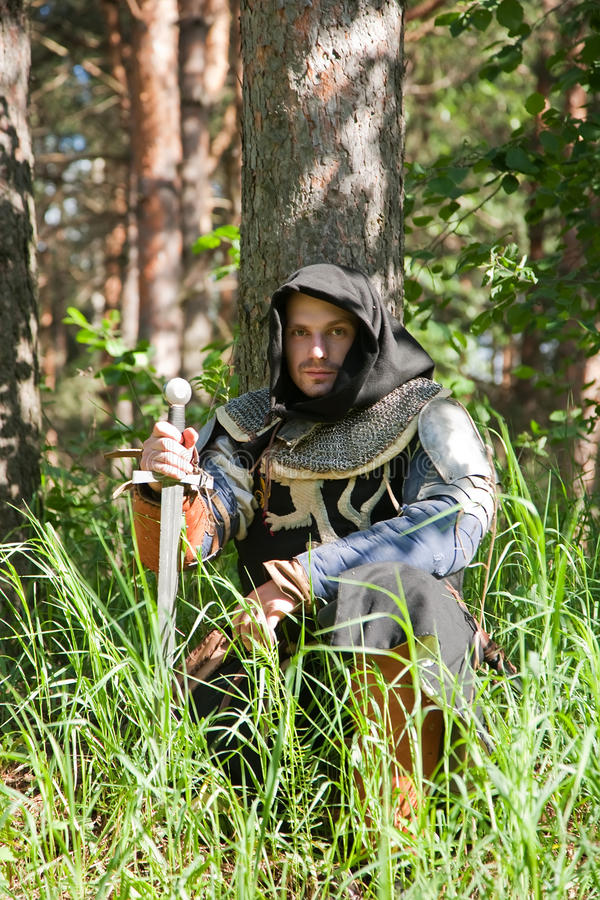 Ritter, der unter dem Baum sitzt lizenzfreie stockfotos