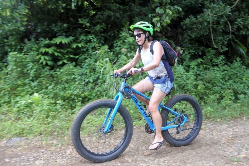 Ritter för ung kvinna skjuter upp mountainbiken i den Rarotonga kocken Islan arkivbilder