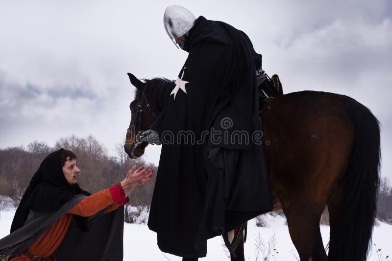 Ritter gibt dem Landarbeiter eine Münze stockbilder