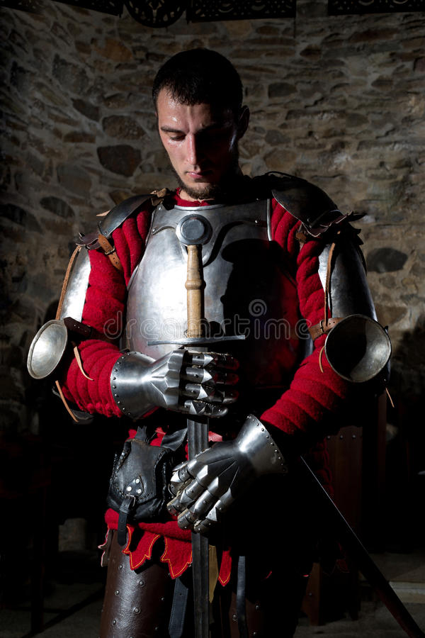 Ritter Standing With Head gebeugt im Gebet und im Halten der Metallklinge gegen alte Steinwand stockfotografie