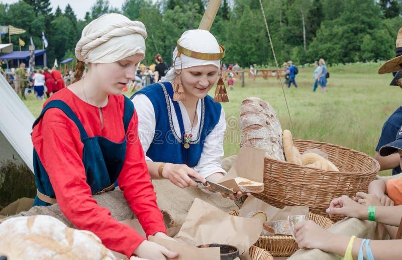RITTER WEG, MOROZOVO, АПРЕЛЬ 2017: Фестиваль европейских средних возрастов Женщины в slavonic одеждах положили pate на хлеб шестк стоковая фотография rf