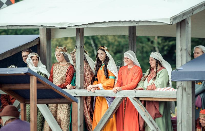 RITTER WEG, MOROZOVO, APRIL 2017: Beautiful ladies in medieval clothes stand in bed watching the tournament of Knights royalty free stock photography