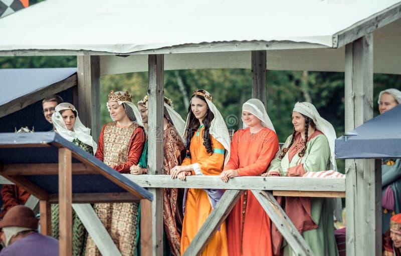 RITTER WEG, MOROZOVO, APRIL 2017: Härliga damer i medeltida kläder står i säng som håller ögonen på turneringen av riddare royaltyfri fotografi