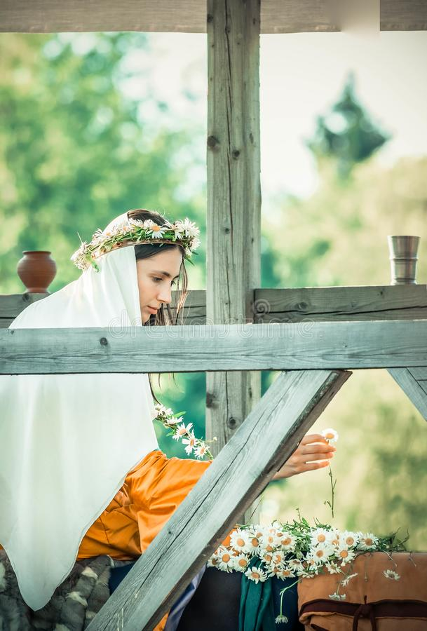 RITTER WEG, MOROZOVO, EM ABRIL DE 2017: A menina bonita nos vestidos longos com o véu no weave principal envolve-se na cabeça de imagens de stock royalty free