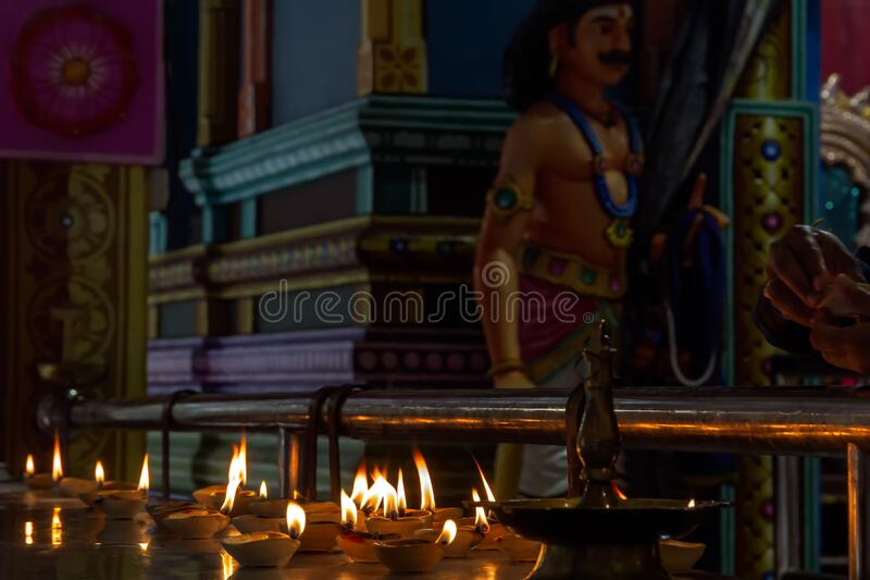 Ritual candles burn in a Hindu temple. On the background of a sculpture of a deity stock photos