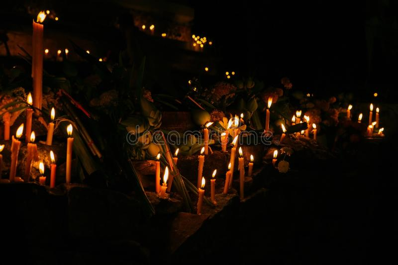 Ritual candles flanking with lotus and other flowers. Around the sacred pagoda during religious ceremony in an ancient temple at night in Thailand stock image