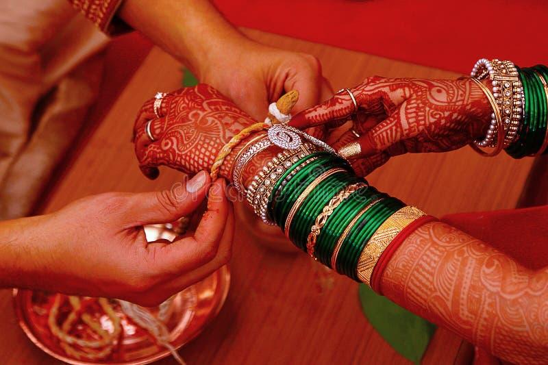 Ritual de la boda, Kankana Dhaarana, un hilo cúrcuma-manchado envuelto alrededor de una raíz de cúrcuma fotos de archivo libres de regalías