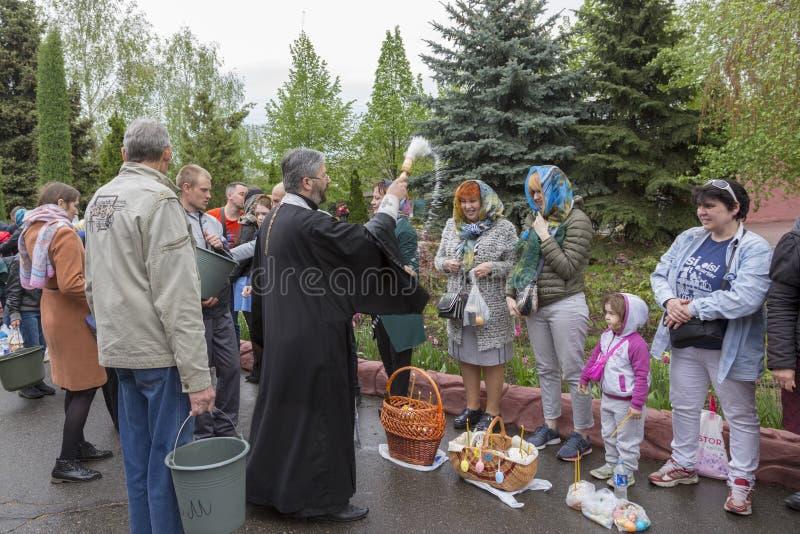 Ritualen av bestänkanden av det invigde vattnet av församlingsboerna av kyrkan under festmåltiden av påsken arkivbild