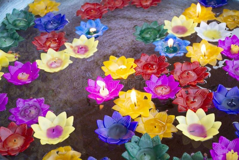 Ritualen som ber den färgrika blommastearinljuset som svävar på vatten för, ber buddha på templet av Thailand royaltyfria bilder