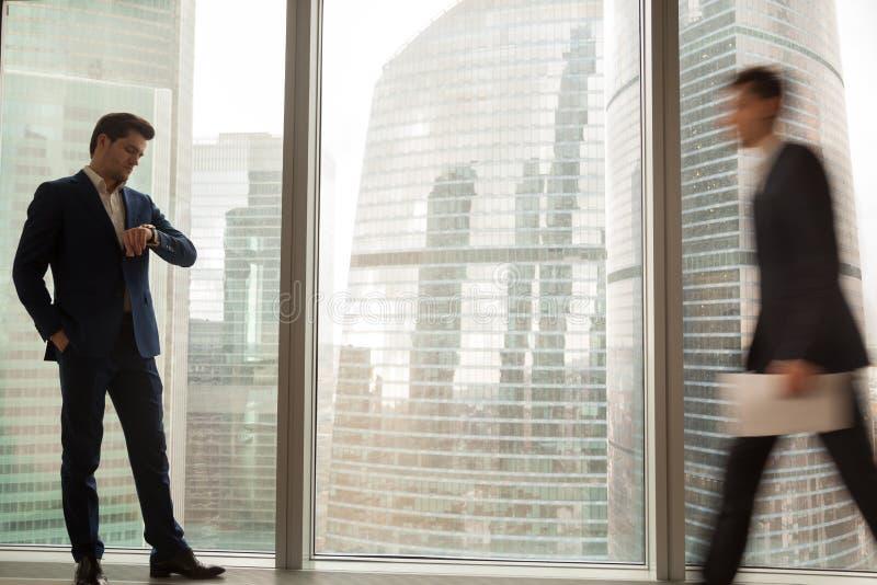 Riunione aspettante dell'uomo d'affari, controllante tempo sull'orologio fotografia stock libera da diritti