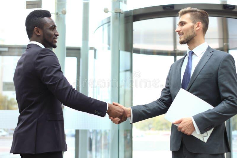 Riunione d'affari Uomo d'affari afroamericano che stringe le mani con l'uomo d'affari caucasico fotografia stock