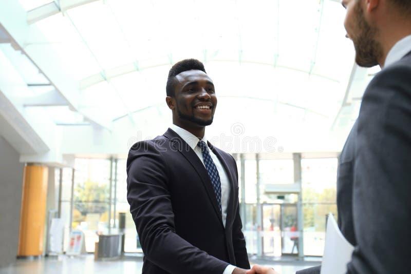 Riunione d'affari Uomo d'affari afroamericano che stringe le mani con l'uomo d'affari caucasico immagini stock libere da diritti