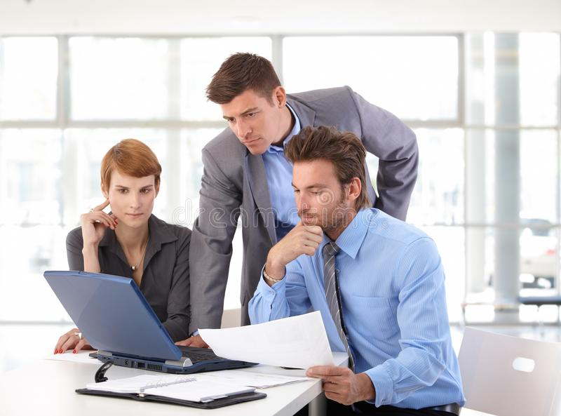 Riunione del gruppo di affari facendo uso del computer portatile all'ufficio fotografie stock