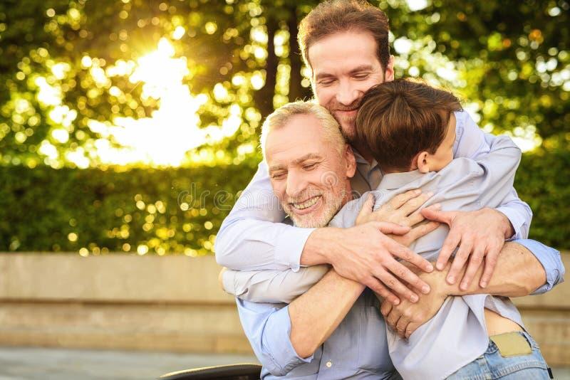 riunione della famiglia Un uomo e un ragazzo sono venuto a vedere il loro nonno che si siede in un parco su una sedia a rotelle immagini stock libere da diritti