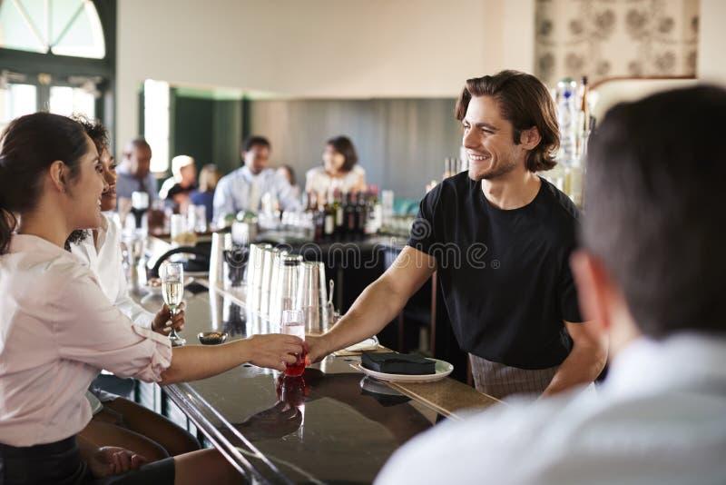 Riunione di Serving Two Businesswomen del barista per dopo le bevande degli impianti immagini stock